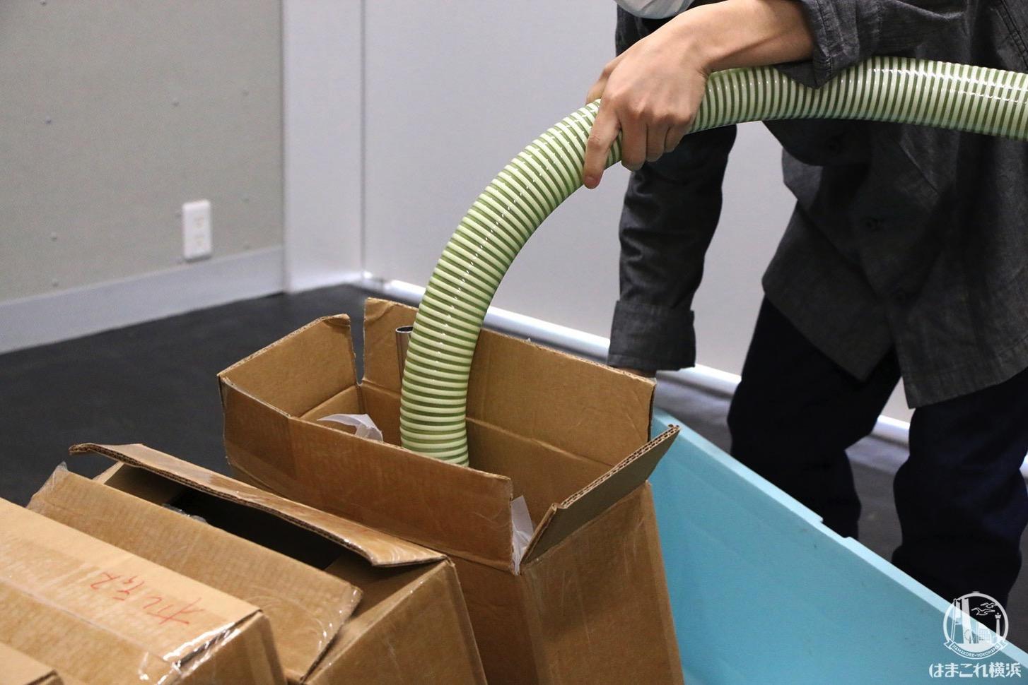 真空した袋から生豆を空気搬送機で送り運ぶシーン